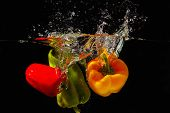 Red green and yellow bellpepper falling into the water with a splash on a black background