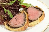 A meal of beef wellington, or boeuf en crout, served with a salad of lollo rosso lettuce, cherry tom