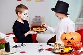 Photo of two eerie boy offering cookies to his twin brother on Halloween day