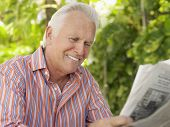Closeup of a smiling mature man reading newspaper outdoors
