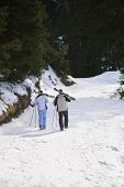 Full length rear view of a skiing couple carrying skis on shoulders on ski slope