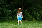 Little girl staring into woods