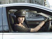 Portrait of female chauffeur in uniform driving a car