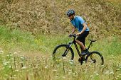 Mountain Biker Riding His Bike Through the Blooming Meadow