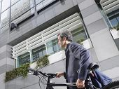 Low angle side view of a businessman carrying bicycle outdoors