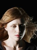 image of windswept  - Closeup of beautiful woman with windswept hair looking down on black background - JPG