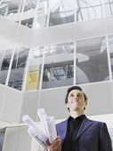 Low angle view of a smiling businessman holding rolled blueprints under arm in atrium of office buil