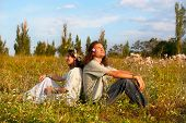 Couple Hippies Sit In The Grass