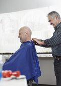 pic of barbershop  - Hairdresser removing cape from senior man after haircut in barbershop - JPG