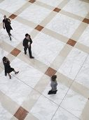 Elevated view of blurred business people walking on tiled floor
