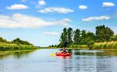 stock photo of kayak  - Girl with paddle and kayak on a small river in rural landscape - JPG