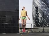 Low Angle View einer jungen Frau, die gegen die Innenstadt von Gebäuden in London überspringen