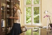 stock photo of shelving unit  - Side view of a young blond woman looking in cabinet in study room - JPG