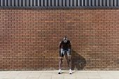 Full length of an African American man resting against brick wall