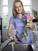 Smiling middle aged woman rinsing and cutting flowers in the kitchen sink