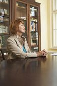 image of shelving unit  - Side view of a middle aged woman sitting at study table in living room - JPG