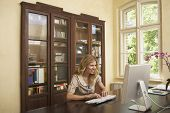 foto of shelving unit  - Smiling young blond woman using computer in study room at home - JPG