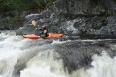Side view of a woman kayaking in rough river