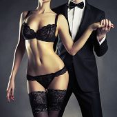 stock photo of erotics  - Art photo of a young couple in sensual lingerie and a tuxedo - JPG