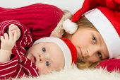 Little girl with baby boy lie in the hats of Santa Claus, focus on a baby.