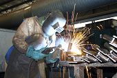 image of factory-worker  - Factory worker welding metal in a factory showing sparks and protective gear - JPG