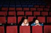 Little boy and girl in an empty cinema hall