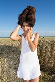 Portrait Of A Girl With Big Hair Over Farm Background