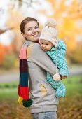 Portrait of young woman and her baby son in park