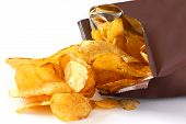 stock photo of crisps  - Open packet of crisps spilling onto a white surface - JPG
