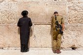 Soldier and orthodox jewish man pray at the western wall, Jerusalem