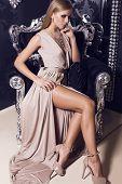 sexy blond in beige silk dress sitting on the black armchair
