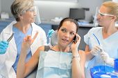 Busy businesswoman at dental surgery calling on phone dentists waiting