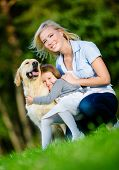 Mother and daughter with golden retriever sitting on the grass and embracing the dog at the summer p