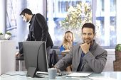 Happy businessman sitting at desk, working, smiling, looking at camera.