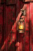 Old rusty kerosene lantern hanged on a rustic wooden wall