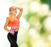 sport, exercise and healthcare - smiling sporty woman with orange towel and water bottle