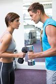 Fit couple lifting dumbbells together facing off at the gym