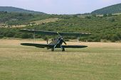 image of biplane  - A vintage camouflage biplane secured to the ground at a grassy airfield - JPG