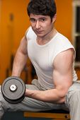 Young Man Lifting Dumbell At Fitness Gym