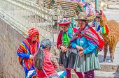 CUZCO, PERU, MAY 1, 2014 - Woman with children, all in traditional attire, bringing a llama to the c