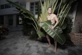 stock photo of implied nudity  - Handsome naked man covered by a palm frond - JPG