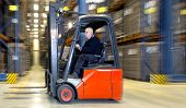 Forklift in a warehouse, driving at speed past the aisles of storage racks
