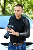 Man near car with photo camera