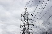 a high voltage transmission line tower against cloudy sky