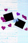 Blank old photos and decorative hearts on color wooden background