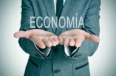 a businessman with the word economia, economy in spanish, in his hands