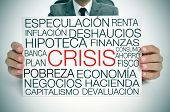 a businessman holding a signboard with different terms in spanish related to the economic crisis con