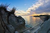 Rocks, sand, sea and a beach with a small cave at sunset, Sithonia