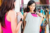Asian young woman choosing dress in fashion store looking at herself in the mirror