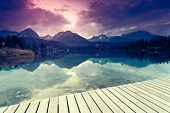 Fantastic mountain lake with berth in National Park High Tatra. Dramatic overcast sky. Strbske pleso, Slovakia, Europe. Beauty world. Retro style filter. Instagram toning effect.